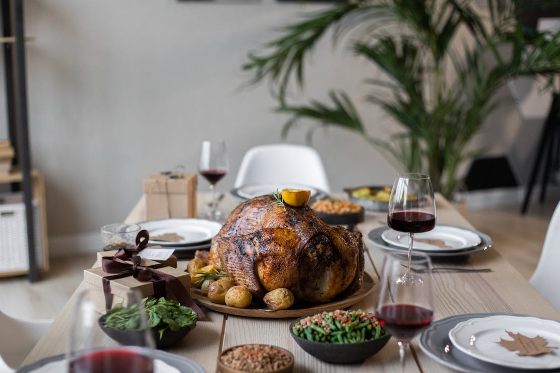 From above of palatable roasted turkey and glasses of wine on wooden table served for celebrating Thanksgiving