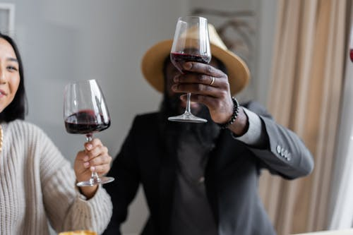 Positive multiracial couple making toast while drinking wine in glasses having festive dinner with guests at home