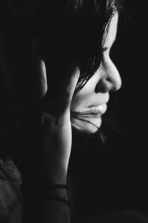 Grayscale Photo of a Woman Touching Her Hair