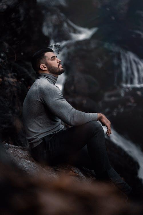 Man in Gray Long Sleeve Shirt Sitting on Rock