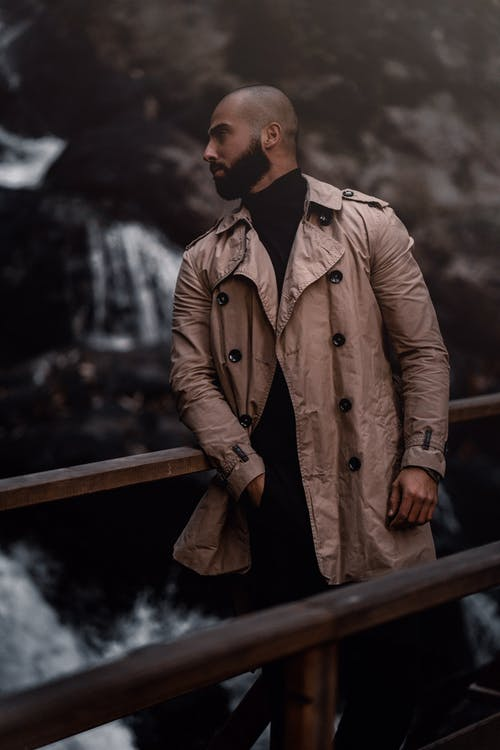 Man in Brown Coat Standing Near Brown Wooden Fence