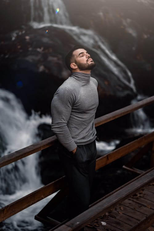 Man in Gray Sweater and Black Pants Standing on Brown Wooden Bridge
