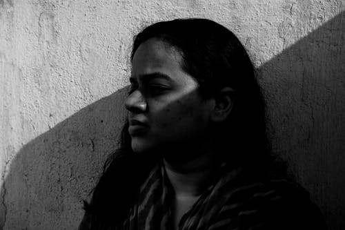 Grayscale Photo of Woman Near a Rough Wall