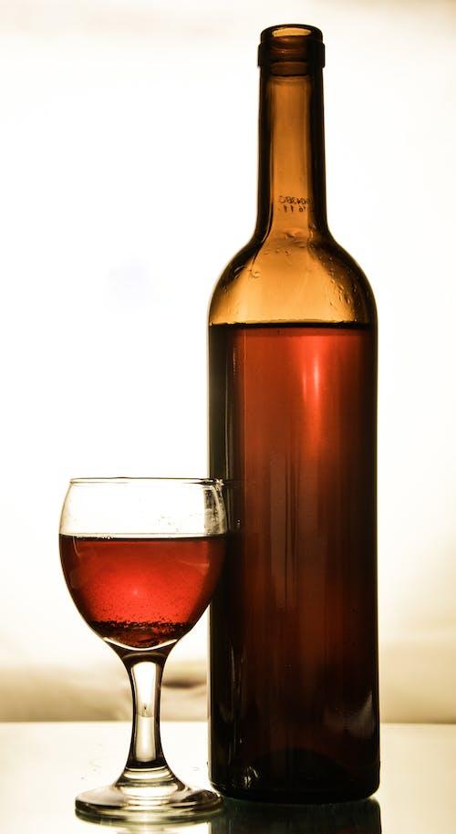 Glass of Wine Beside a Bottle of Wine