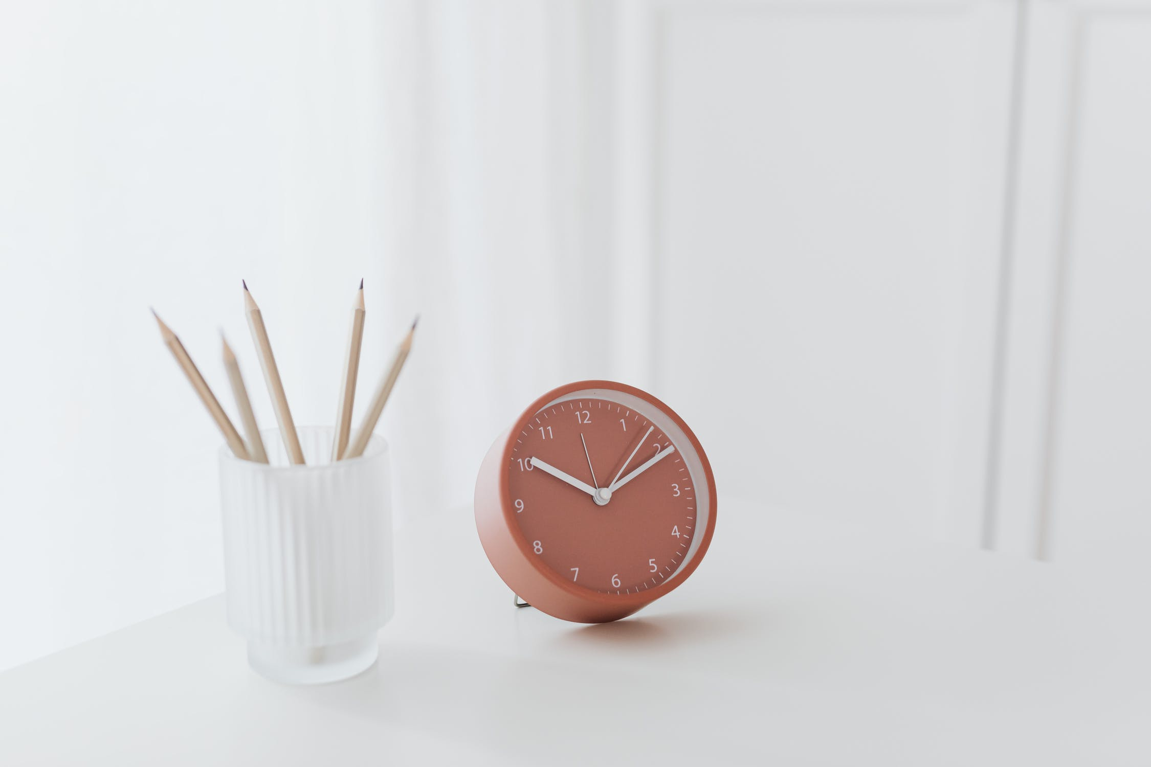 Peach clock on white table depicting 24 hour nature of customer support with conversational ai