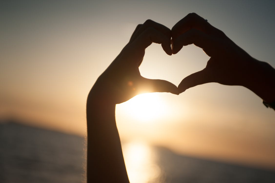 Person Rising Hands Forming Heart Silhouette