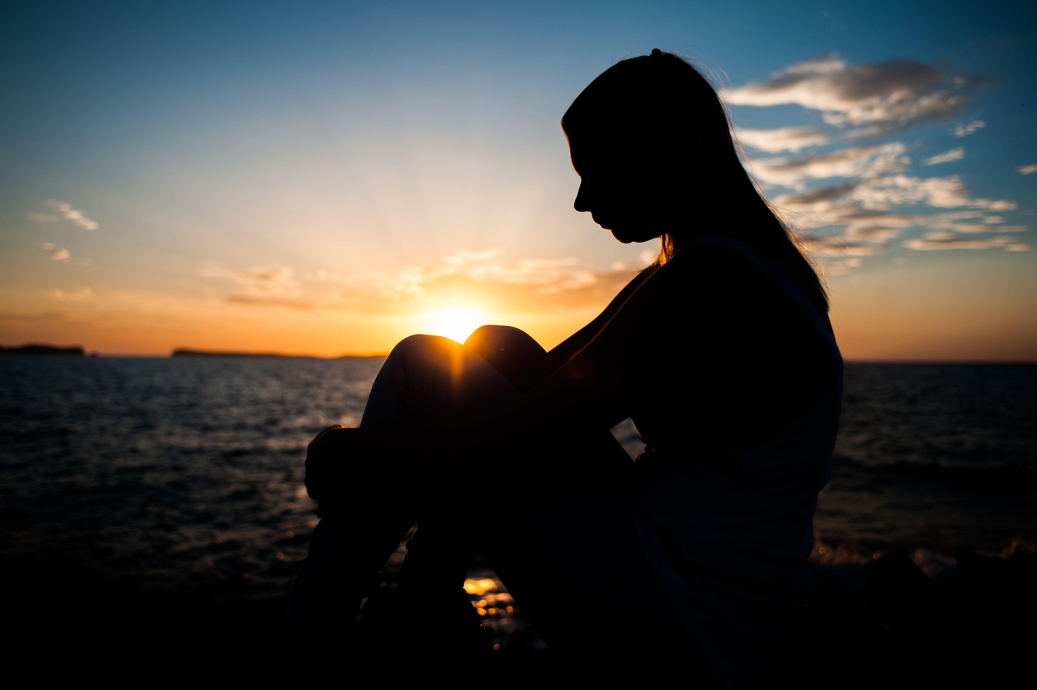 Silhouette of Person Sitting Outdoors