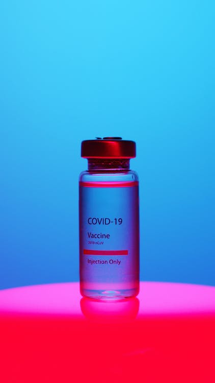 A Close-Up View of a Covid-19 Vaccine Vial on Blue Background