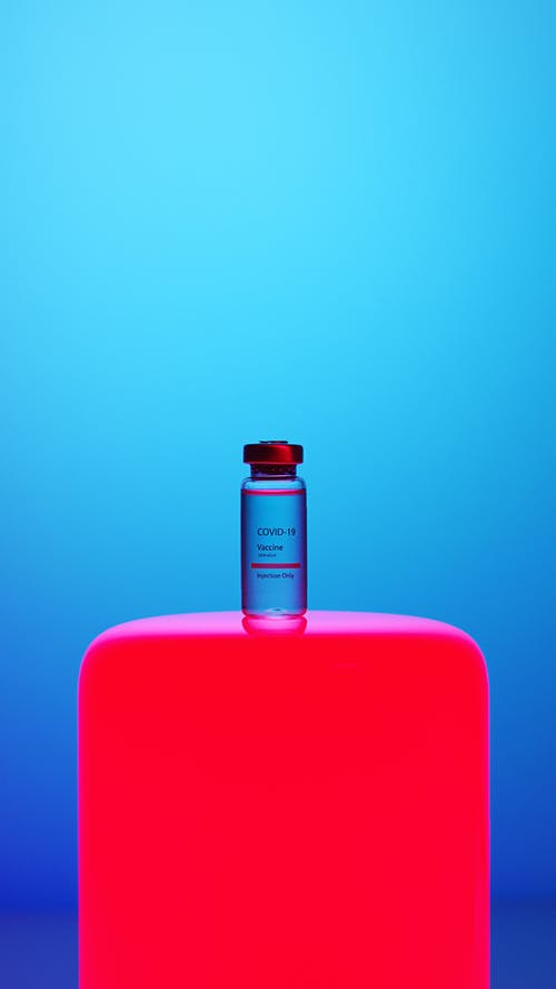 A Covid-19 Vaccine Vial on Blue Background