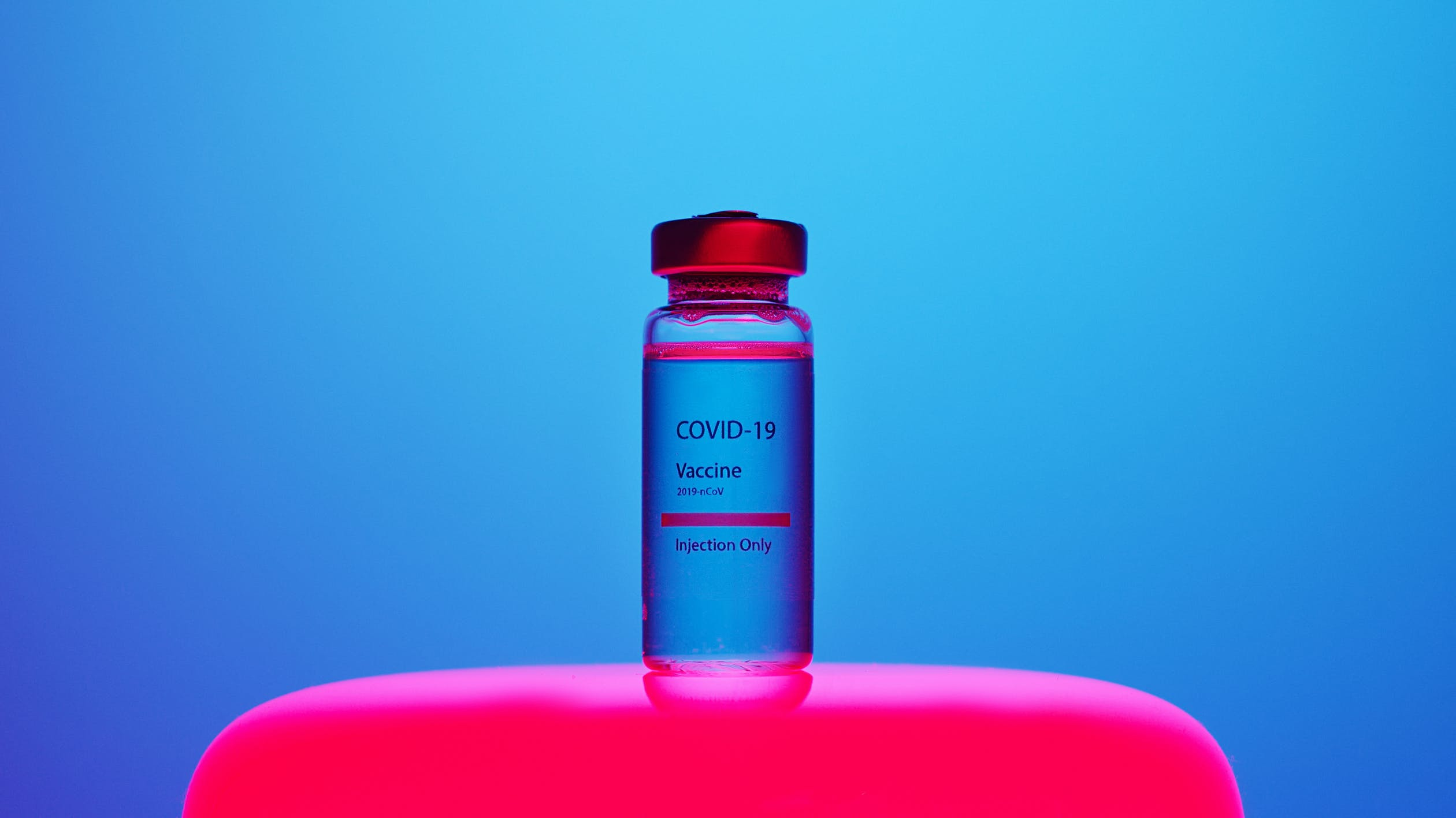 A vial reading COVID-19 Vaccine sits on a red table with a blue backdrop