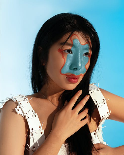 Portrait of Asian woman with painted face looking away putting hand on hair while standing on blue background