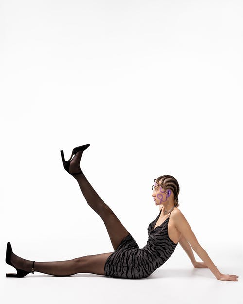 Woman with creative hairstyle sitting on floor with leg raised
