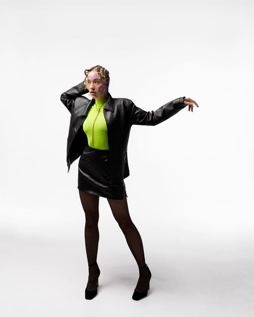 Stylish woman in leather jacket standing with arm raised gracefully
