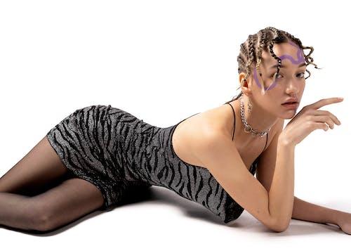 Beautiful graceful slim female with African braids wearing black mini dress lying on floor against white background in photo studio