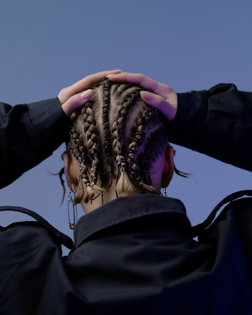 Back view unrecognizable female with African braids hairdo wearing black jacket touching head while standing against dark blue wall in studio