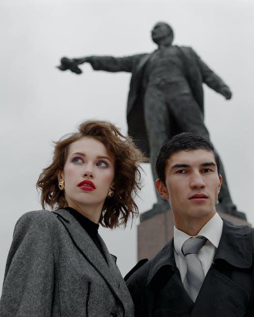 Fashionable couple standing against Lenin monument