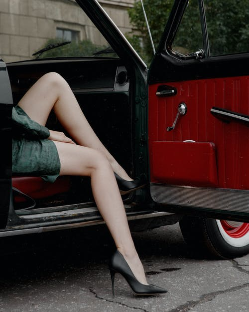 Crop anonymous stylish female in high heel shoes sitting gracefully in retro car passenger seat