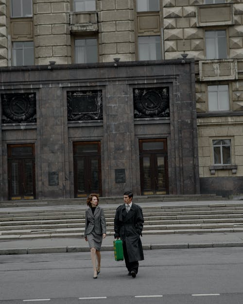 Full body young couple wearing trendy outerwear carrying green retro suitcase and crossing road against majestic stone building