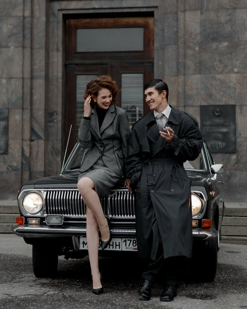 Fashionable young multiethnic couple smiling while flirting together leaning on vintage car on street