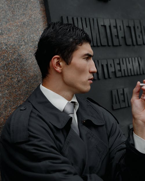 Side view of confident young ethnic male entrepreneur in formal clothes and coat smoking cigarette and looking away thoughtfully while resting on street during break
