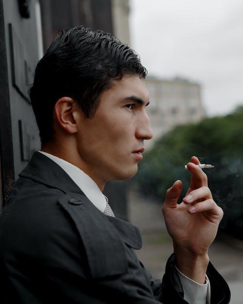 Self esteem young ethnic man smoking cigarette on city street