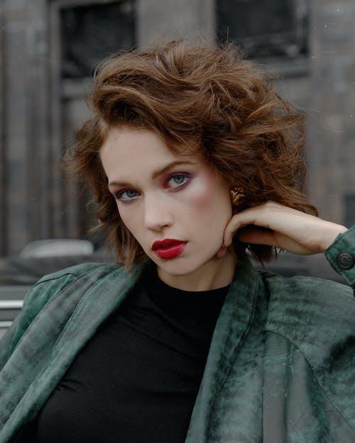 Stylish woman in jacket and makeup looking at camera
