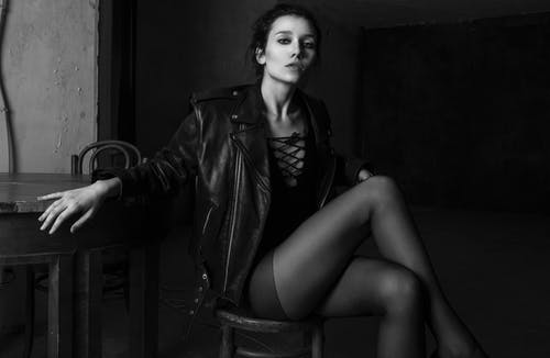 Trendy feminine model in nylon tights on chair