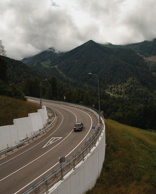 From above of automobile driving on fenced asphalt road near high mountains with trees