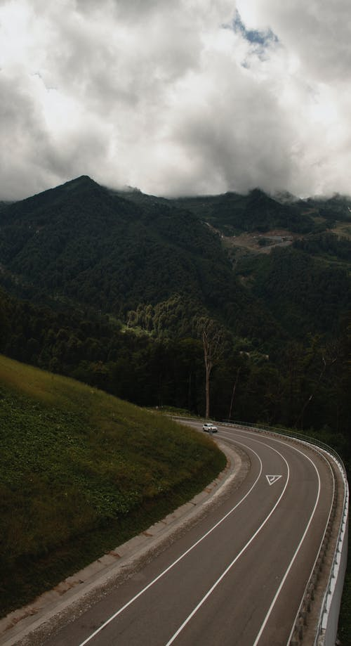Car on road between green mountains under cloudy sky
