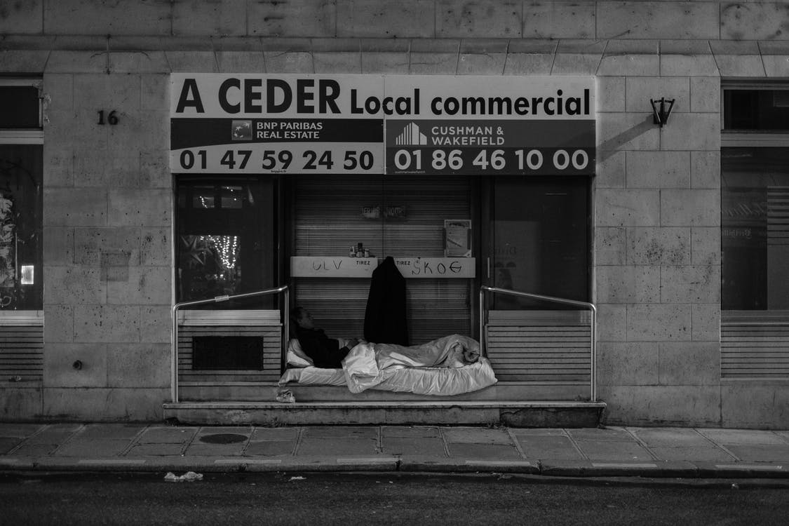 Black and white of homeless man lying on mattress with blanket placed on street near building in city in daytime