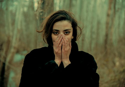 Woman in Black Coat Covering Her Face With Her Hand