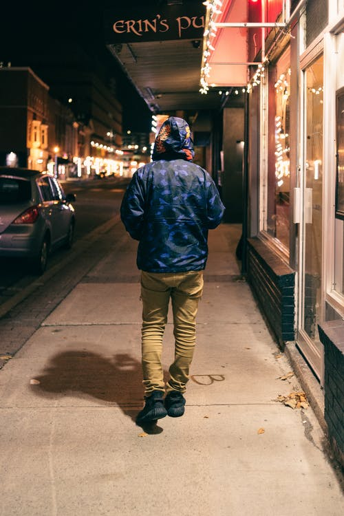 Unrecognizable man walking on pavement in evening town