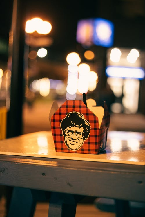 Takeaway container with checkered ornament and face illustration on table in shiny light at night