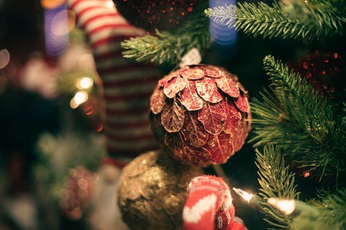 Decorative cone on fir tree with glowing garland