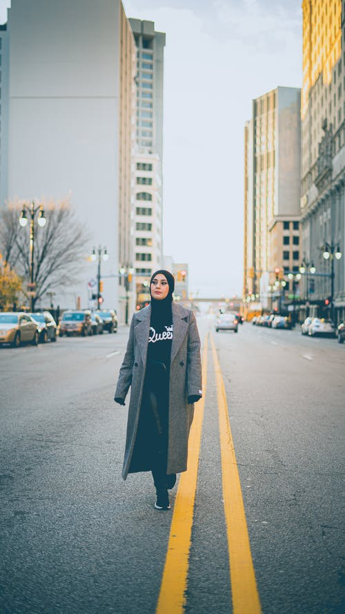 Islamic woman in hijab and coat walking on asphalt road