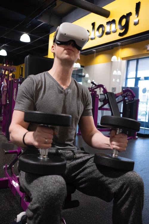 Man in Gray Crew Neck T-shirt and Black Sunglasses Sitting on Black and Purple Exercise
