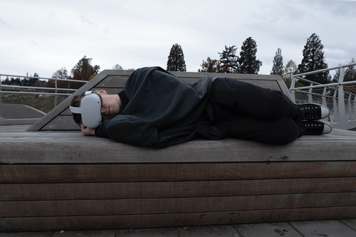 Man in Black Pants Lying on Brown Wooden Bench