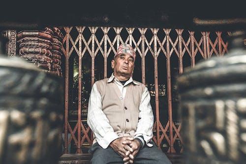 Pensive Asian man sitting near street metal fence