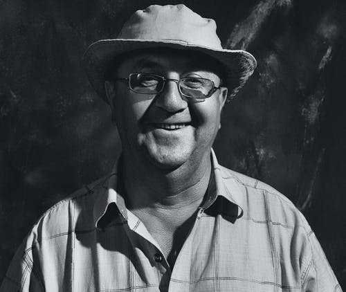 Grayscale Photo of a Man Smiling