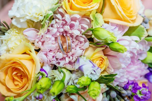 Closeup of colourful romantic bouquet of flowers with golden wedding rings for couple