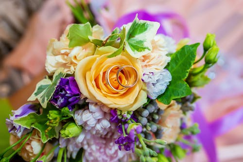 Bridal bouquet of fresh flowers and golden rings