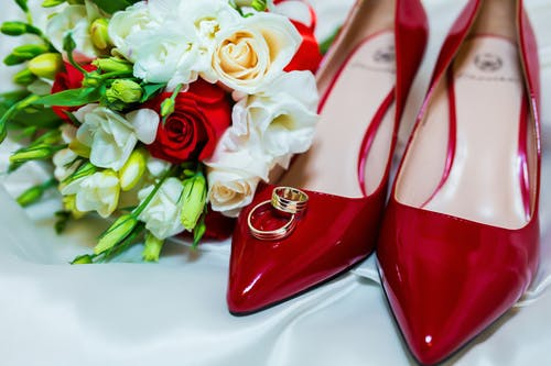 Composition with elegant bridal high heels red shoes wedding bouquet and gold rings