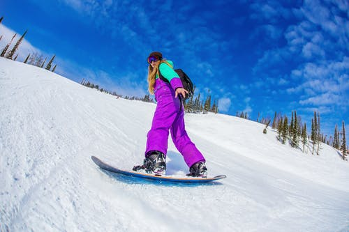 Woman in Pink Jacket and Blue Pants Riding Blue Snowboard