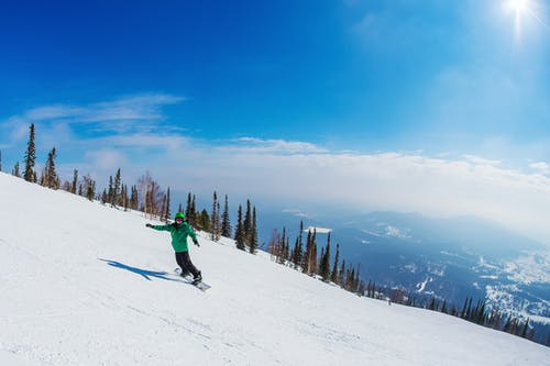Person in Green Jacket and Blue Pants Riding Ski Blades on Snow Covered Mountain