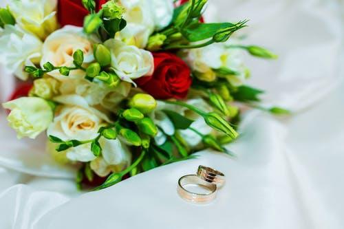 Bouquet of roses placed on white sheet near wedding rings in light room