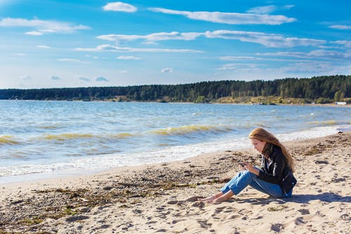 Woman in Blue Jacket and Blue Denim Jeans Sitting on Brown Sand Near Body of Water