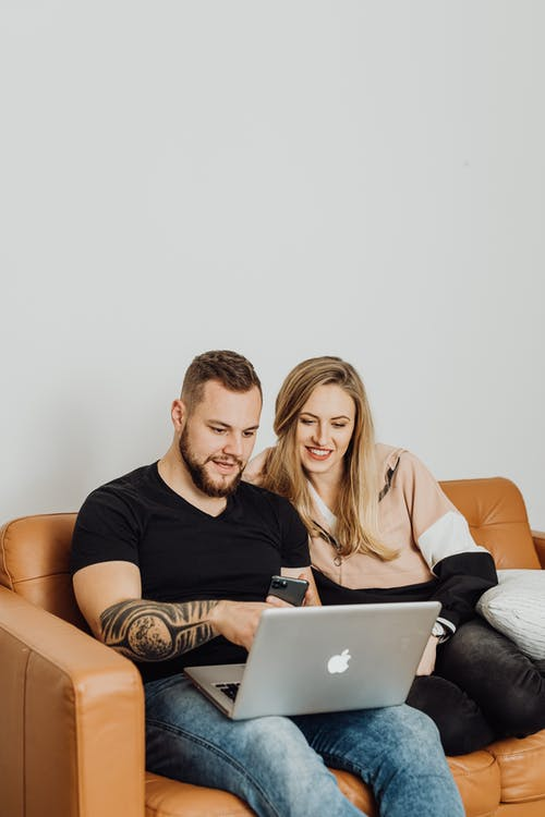 Couple Sitting on Brown Couch