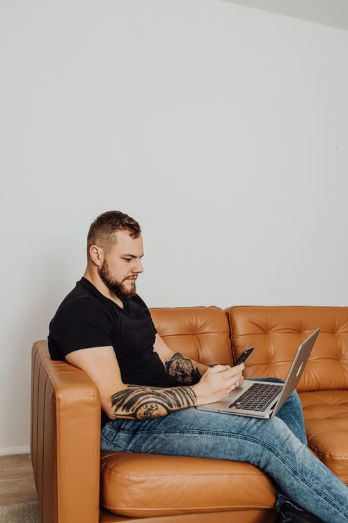 A Man Using Smartphone while Sitting on the Couch