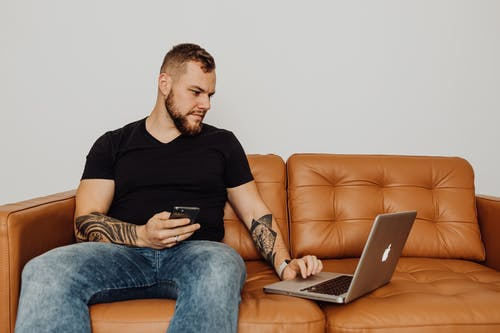 Photo of a Man in a Black Shirt Using His Laptop while Sitting on a Brown Leather Sofa