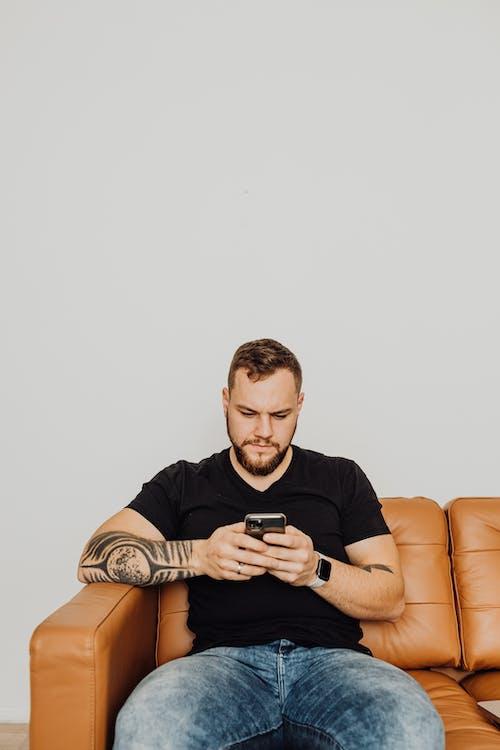 Photos gratuites de à la maison, chemise noire, en utilisant un téléphone portable